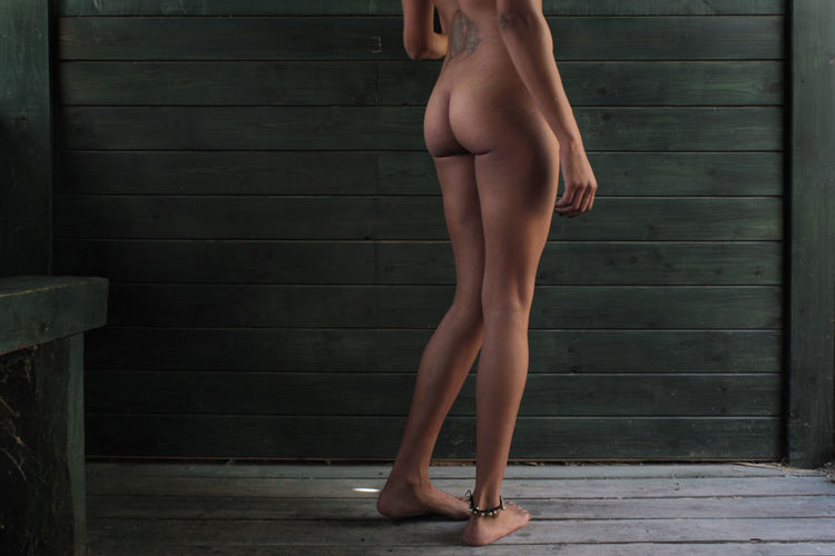 Low section of naked woman standing on wooden floor