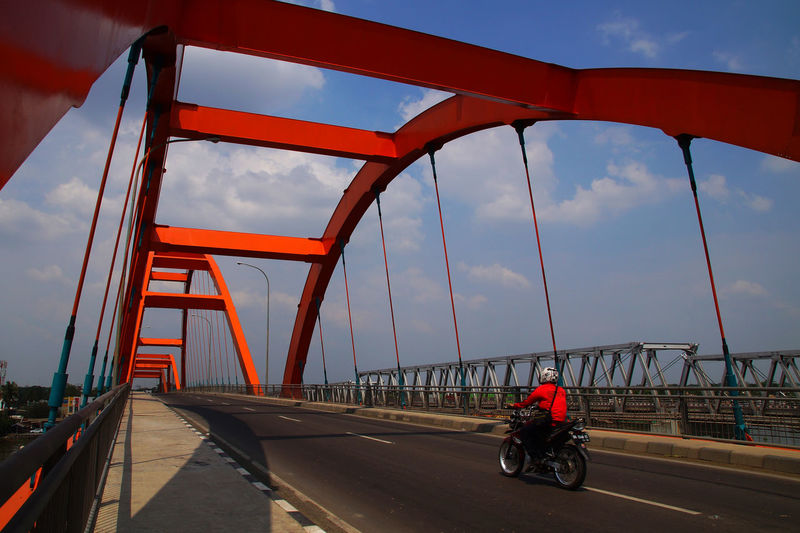 Man riding bicycle on bridge against sky in city
