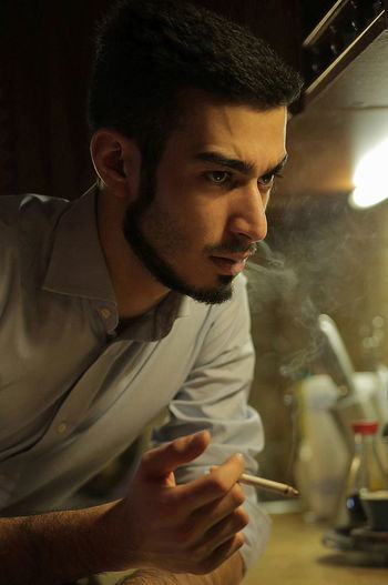 Thoughtful Businessman Smoking While Leaning On Kitchen Counter