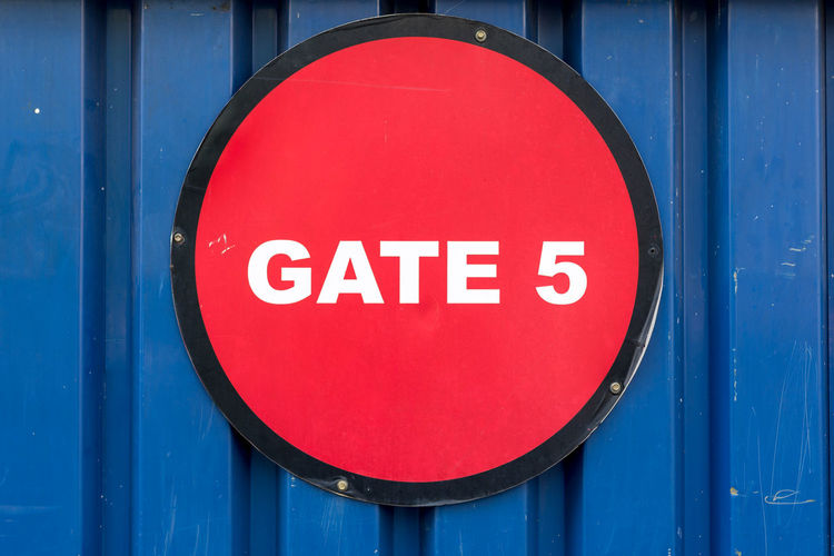 Close-up of gate text on corrugated iron