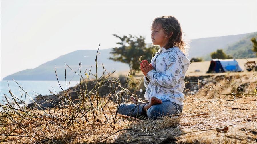 Full length of girl sitting on land
