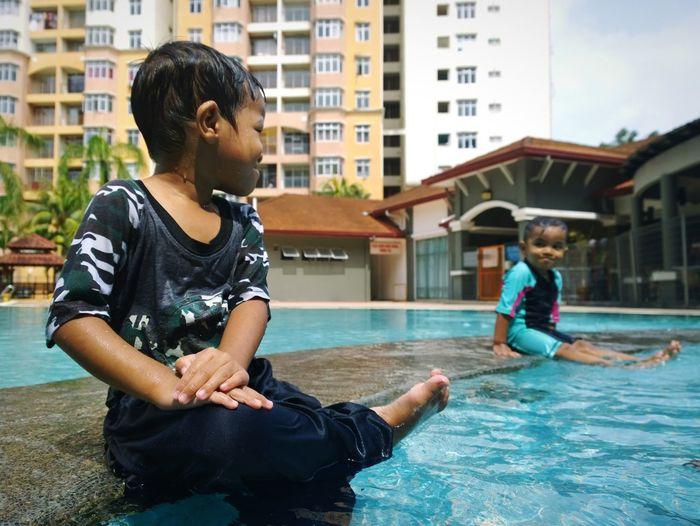 Full length of boys sitting in swimming pool