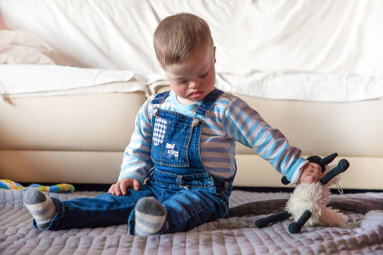 Babyboy Bed Casual Clothing Child Childhood Domestic Room Down Syndrome Front View Full Length Furniture Indoors  Innocence Leisure Activity Lifestyles Males  Men Mental Health  One Person Sitting Sofa Toy