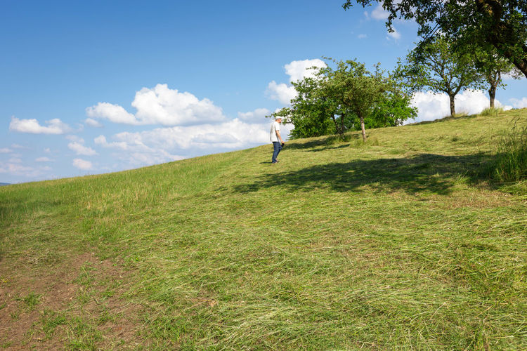 man on field against sky Baum Beauty In Nature Cloud - Sky Day Environment Field Full Length Grass Green Color Growth Juni Land Landscape Leisure Activity Lifestyles Nature Non-urban Scene One Person Outdoors Plant Real People Sky Tree