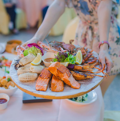 Close-up of woman preparing food in plate on table
