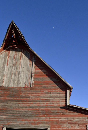 Small moon in background Abandoned Building Exterior Built Structure Day Low Angle View Moon In Distance Outdoors Red Barn Roof Sky