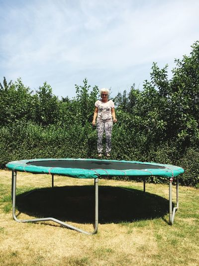 Woman Levitating Over Trampoline Against Plants