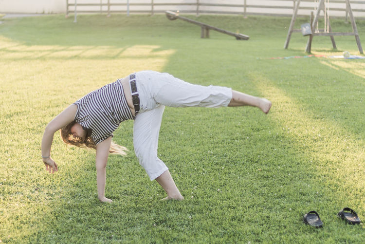 Young woman practicing cartwheel at playground