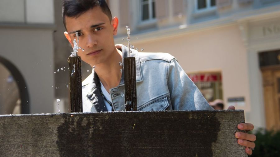 Portrait of teenage boy standing against water fountains