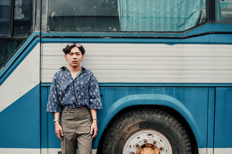 Portrait of man standing against bus