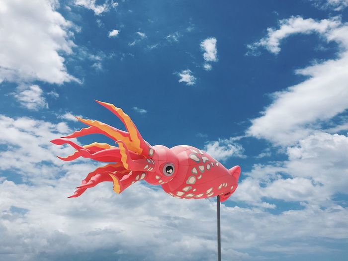 Low angle view of octopus shape windsock against sky
