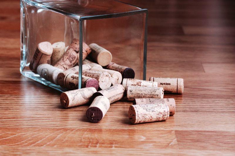 Wine Corks In Glass Container On Hardwood Floor