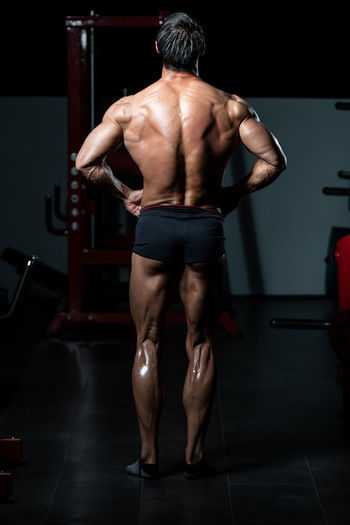 Rear view of shirtless man standing at home