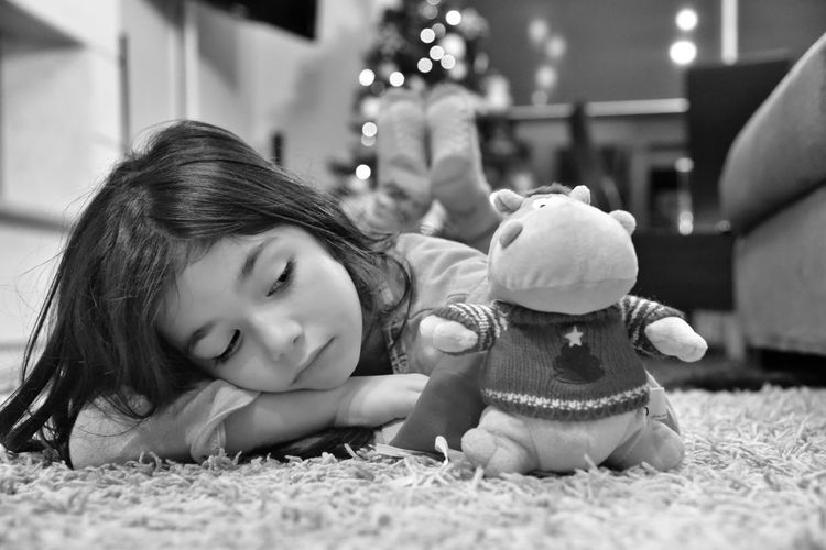 Close-up of sad girl with toy lying on carpet at home
