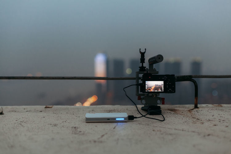 Close-up of illuminated camera and power charger on retaining wall against sky