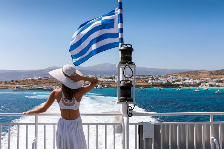 Woman in white dress watching the beauty of the Cyclades island from a ferry boat in Greece Blue Clear Sky Cyclades Day Ferry Flag Greece Greek Hat Koufonisia Lifestyles Nautical Vessel One Person Outdoors Rear View Scenics Sea Sky Standing Sun Hat Sunlight Travel Travel Destinations Vacations Water