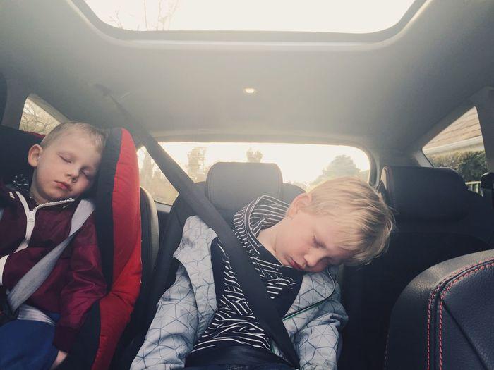 Children sleeping in backseat of car
