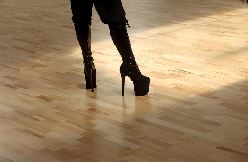 Low section of woman wearing high heels standing on hardwood floor