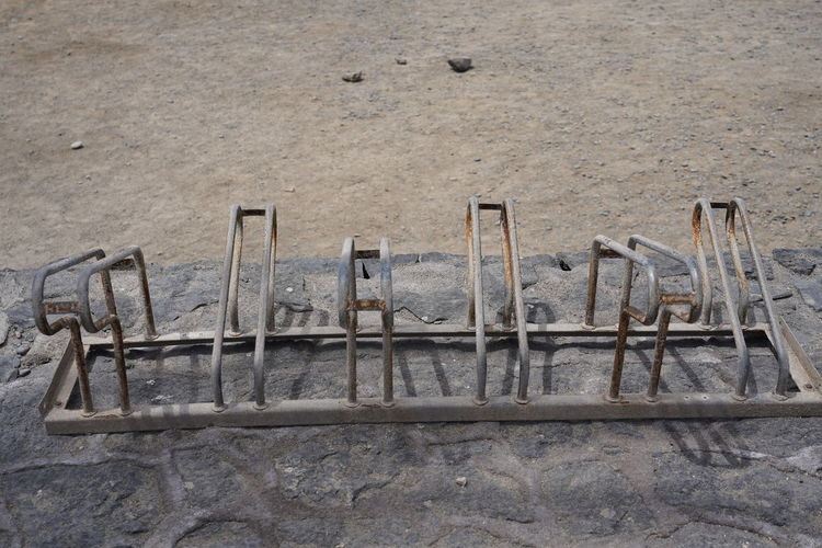 High angle view of old wooden posts on sand