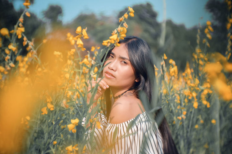 Portrait of woman by yellow flowering plants