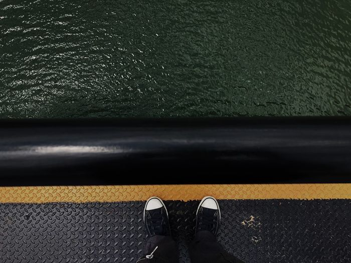 Low section of person standing boat deck over sea