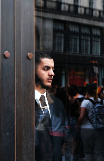 Young man looking away while standing against door