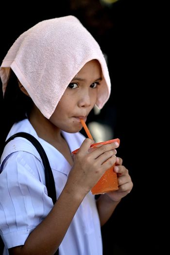 Close-up of girl drinking juice from glass outdoors
