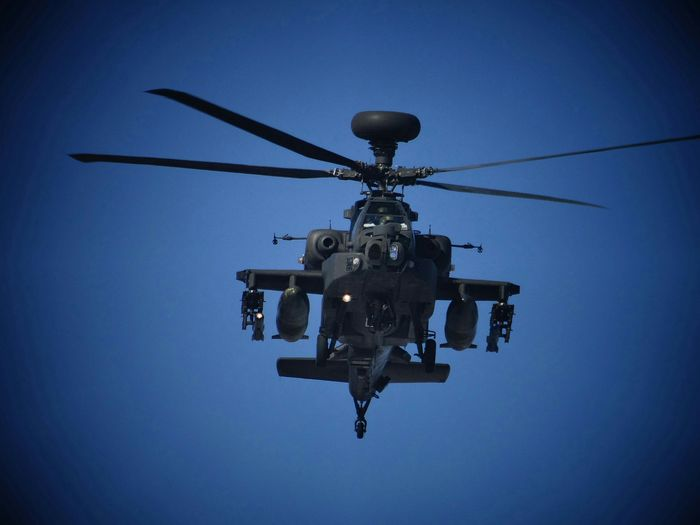Low angle view of apache helicopter flying against clear blue sky