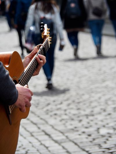 Cropped image of man playing guitar on street