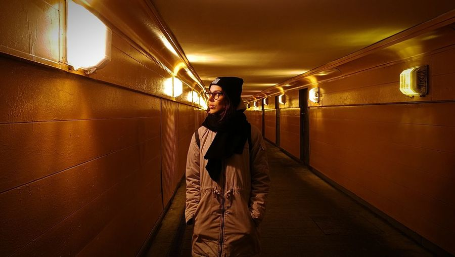 Woman standing in illuminated underground walkway