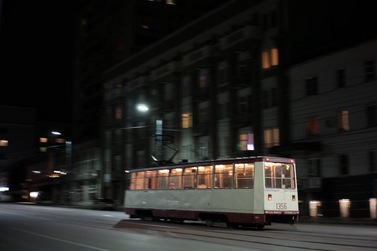 TRAIN ON ILLUMINATED STREET IN CITY