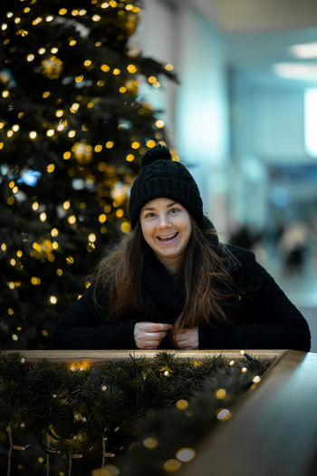 Portrait of a smiling young woman with christmas tree