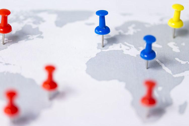 Close-up of thumbtacks on world map