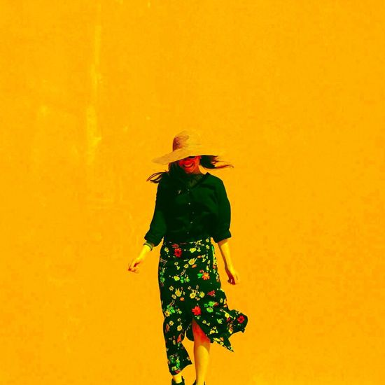 Rear view of woman standing against yellow wall