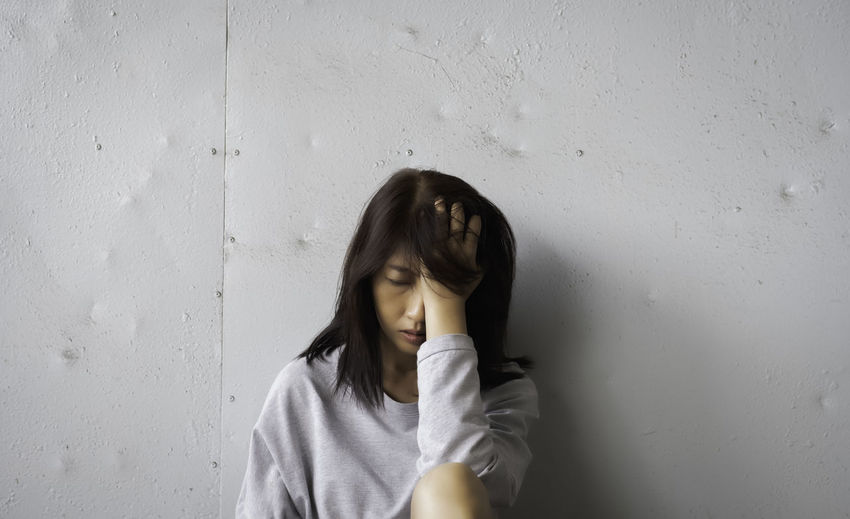 Unhappy woman put hand touch her head,with upset and sad feeling,blurry light around