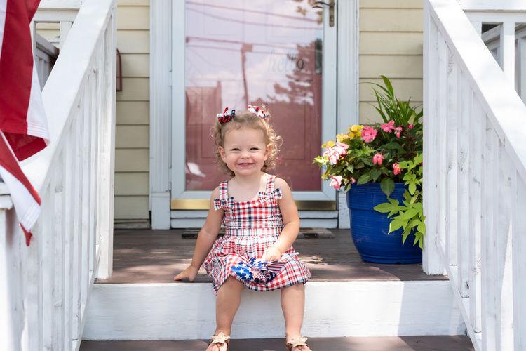 Full length portrait of smiling girl standing against building