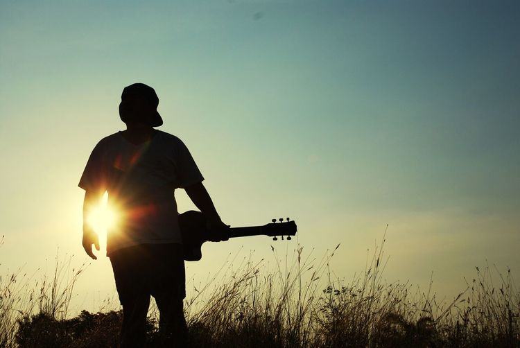 Silhouette man with guitar standing on field against sky during sunset