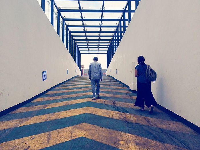 Rear view of tourists walking on pedestrian walkway