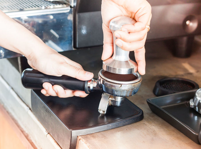 Cropped hands crushing coffee beans with equipment