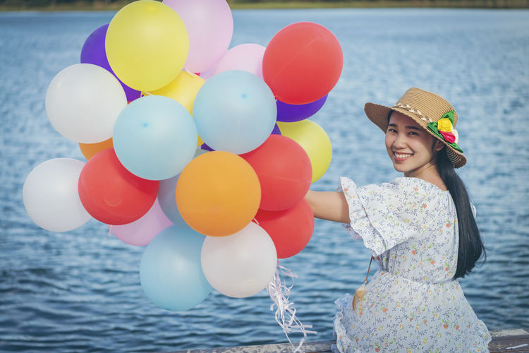 Rear view of woman holding balloons at sea