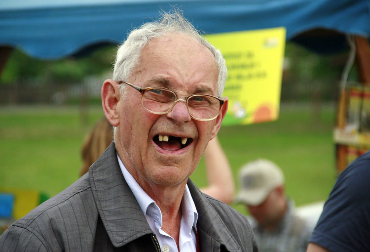 Portrait of gaped tooth senior man smiling while standing at park