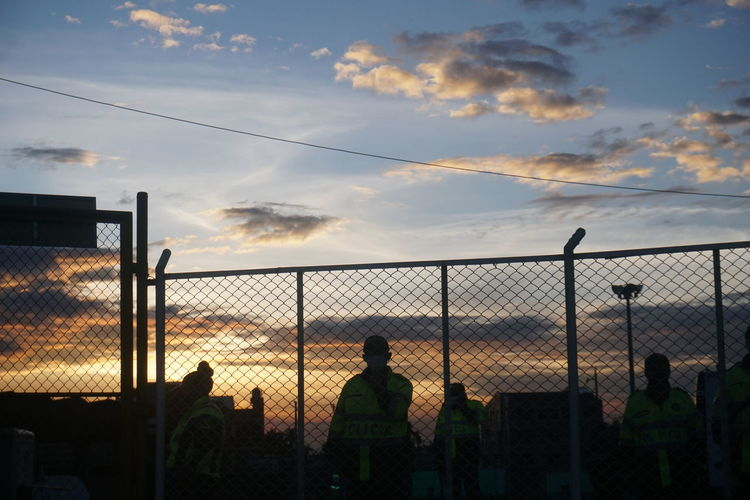 Rear view of silhouette man standing by chainlink fence against sky during sunset