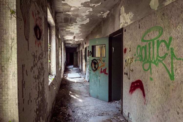 Mental Hospital  Architecture Graffiti Built Structure Abandoned Building Indoors  No People Text Day Old Wall - Building Feature Damaged Direction Arcade Entrance Corridor Messy The Way Forward Communication Dirty Deterioration Ceiling