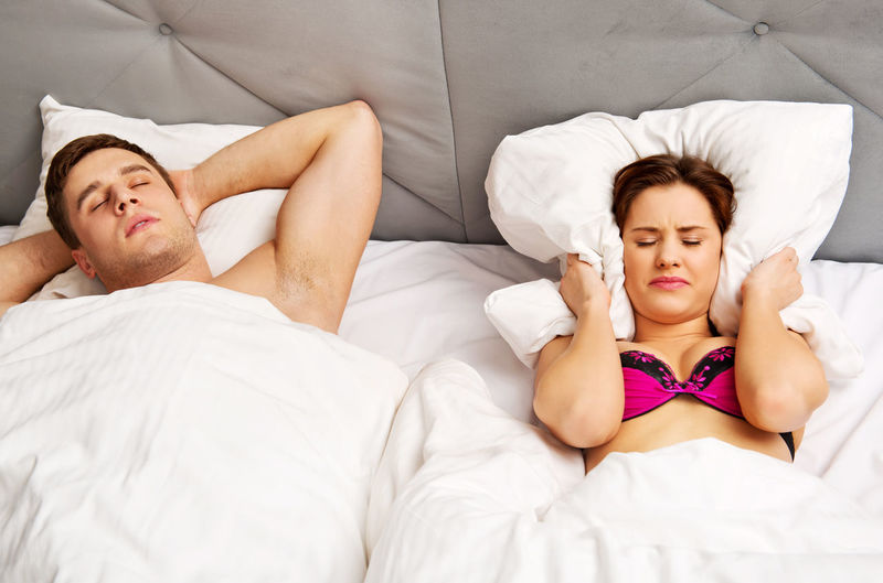 High Angle View Of Woman Covering Ears While Man Snoring In Bed At Home