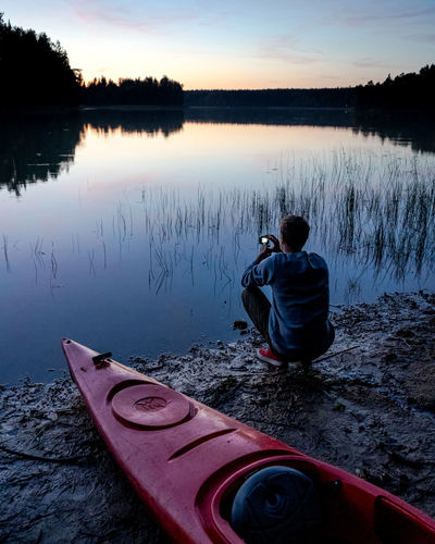 Rear view of man sitting by lake against sky during sunset