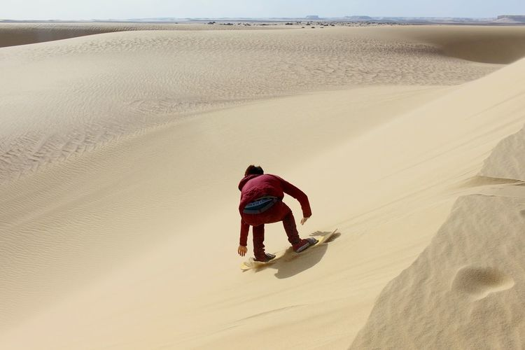 Rear view of man sandboarding