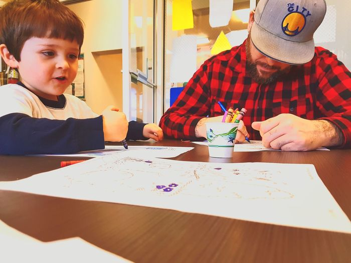 Father And Son Drawing With Crayons In Papers At Home