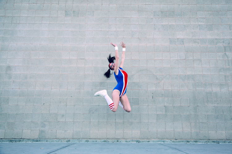 Full Length Of Cheerful Female Gymnast In Leotard Jumping Against Wall