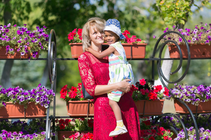 Portrait of smiling mother carrying daughter against flowers in window boxes