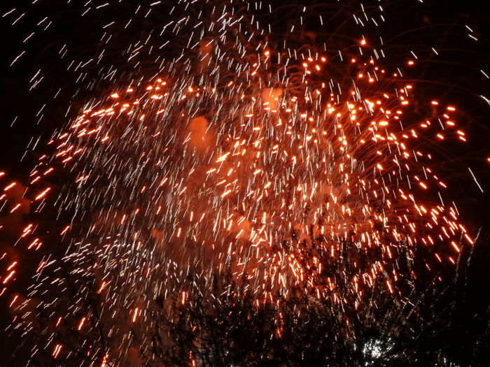 Motion Firework Night Event Celebration Illuminated Blurred Motion Firework Display Long Exposure Glowing No People Arts Culture And Entertainment Heat - Temperature Low Angle View Exploding Firework - Man Made Object Nature Sparks Red Orange Color Light Black Background